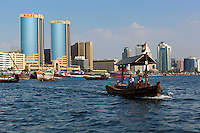 United Arab Emirates, Dubai: Abra and cargo ships along Dubai Creek | Vereinigte Arabische Emirate, Dubai: Abra und Frachtschiffe am Dubai Creek