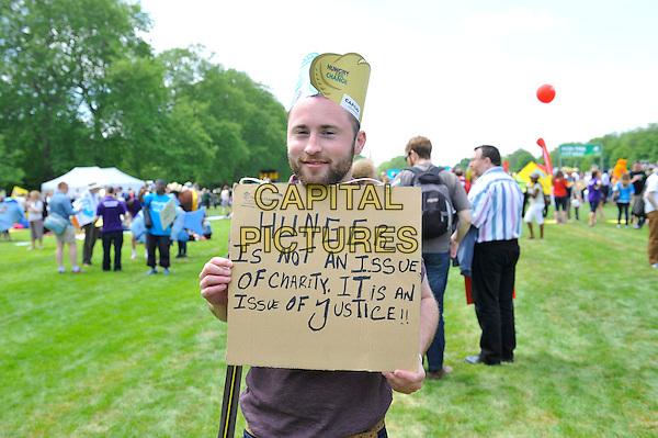 Fan<br /> attending The Big IF, Hyde Park, London, England. <br /> 8th June 2013<br /> half length brown costume gv general view concert goers hat brown cardboard sign hunger is not an issue of charity it is an issue of justice <br /> CAP/MAR<br /> &copy; Martin Harris/Capital Pictures