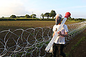 A protester in an Osama Bin Laden mask stands at the outer perimeter barbed wire fence around the G8 summit venue at Lough Erne on June 17, 2013 in Enniskillen, Northern Ireland. The two day G8 summit, hosted by UK Prime Minister David Cameron, is being held in Northern Ireland for the first time. Leaders from the G8 nations have gathered to discuss numerous topics with the situation in Syria expected to dominate the talks. Photo/Paul McErlane