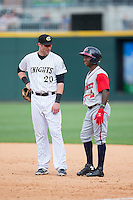 Charlotte Knights first baseman Danny Hayes (20) chats with Ozzie Albies (2) of the Gwinnett Braves during the game at BB&T BallPark on May 22, 2016 in Charlotte, North Carolina.  The Knights defeated the Braves 9-8 in 11 innings.  (Brian Westerholt/Four Seam Images)