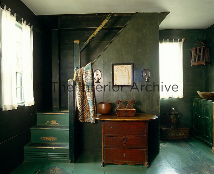 In this entrance hall the wide wooden wall panelling and floorboards have been painted in two different tones of green