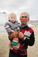 Mongolia, Bayan-Ulgii, Ulgii, Altai Mountains. Man with baby.
