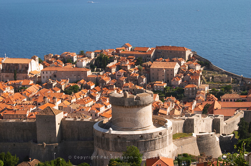 View from above of the old town with city walls and fort brick coloured rooftops roof tops detail of one of the wall fortification towers, Minceta Tower Dubrovnik, old city. Dalmatian Coast, Croatia, Europe.