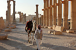Local man and his camel on the colonnaded street in ancient Palmyra, Syria. Palmyra was an important city of central Syria, located in an oasis 215 km northeast of Damascus and 180 km southwest of the Euphrates river. It had long been a vital caravan city for travelers crossing the Syrian desert and was known as the Bride of the Desert.