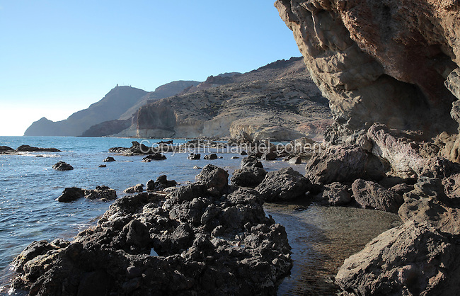 Rocky coastline of volcanic rocks and lava formations, seen from the end of Monsul beach, the most famous and picturesque beach in the park, in the Cabo de Gata-Nijar Natural Park, Almeria, Andalusia, Southern Spain. The park includes the Sierra del Cabo de Gata mountain range, volcanic rock landscapes, islands, coastline and coral reefs and has the only warm desert climate in Europe. The park was listed as a UNESCO Biosphere Reserve in 1997 and a Specially Protected Area of Mediterranean Importance in 2001. Picture by Manuel Cohen