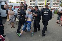 """Auf einer Buergerversammlung mit ca. 500 Teilnehmern im Berliner Plattenbaubezirk Hellersdorf entlud sich am Dienstag den 9. Juli 2013 der blanker Rassismus gegen eine geplante Unterkunft fuer syrische Buergerkriegsfluechlinge. Etwa 2/3 Anwesende aeusserten, es solle """"zuerst was fuer Deutsche getan werden"""", """"das Heim anzuenden"""", """"Wer sein Heimatland verlaesst ist ein Verraeter"""", """"Wer denkt an unsere Kinder"""" und aehnliche Parolen gegen das Fluechtlingsheim. Veranstaltungsteilnehmer, die Verstaendnis fuer die Buergerkriegsfluechtlinge aeusserten, wurden niedergebruellt.<br />Im Bild: Einer der rechten Veranstaltungsteilnehmer wird von der Polizei abgefuehrt.<br />9.7.2013, Berlin<br />Copyright: Christian-Ditsch.de<br />[Inhaltsveraendernde Manipulation des Fotos nur nach ausdruecklicher Genehmigung des Fotografen. Vereinbarungen ueber Abtretung von Persoenlichkeitsrechten/Model Release der abgebildeten Person/Personen liegen nicht vor. NO MODEL RELEASE! Don't publish without copyright Christian-Ditsch.de, Veroeffentlichung nur mit Fotografennennung, sowie gegen Honorar, MwSt. und Beleg. Konto:, I N G - D i B a, IBAN DE58500105175400192269, BIC INGDDEFFXXX, Kontakt: post@christian-ditsch.de<br />Urhebervermerk wird gemaess Paragraph 13 UHG verlangt.]"""