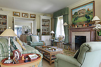 A cream and green sitting room with large armchairs and a tartan patterned sofa. The curtains and armchairs in Colorado Verveine are from Manuel Canovas