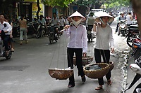 Hanoi<br /> , Vietnam - 2007 File Photo -<br /> <br /> Two young Vietnamese women wearing a traditional hat carries  baskets loaded with  items for sale, in Hanoi.<br /> <br /> <br /> <br /> <br /> photo : James Wong-  Images Distribution