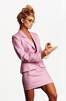 Photo of a businesswoman in a pink skirt suit making notes on a pad in her hand.