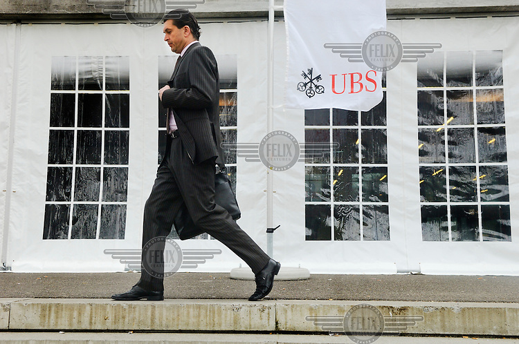 A businessman leaves the annual general meeting for shareholders of UBS, Switzerland's largest bank. The Swiss banking industry holds an estimated 4,000 billion Swiss Francs (USD 4,240 billion) in assets, more than half of it foreign, including CHF 880 billion in undeclared European assets alone, benefiting from the country's famous banking secrecy laws.
