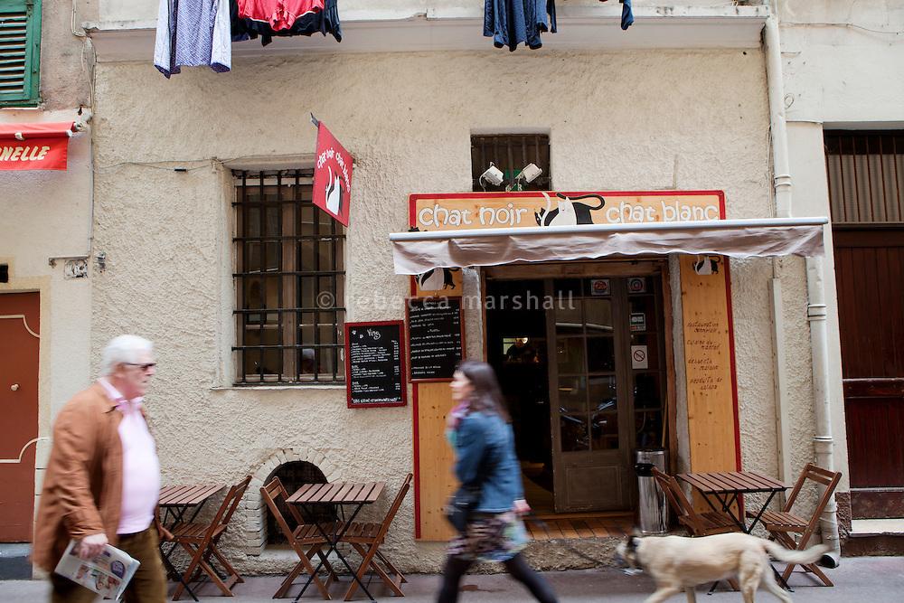 Pedestrians pass by the restaurant 'Chat Noir, Chat Blanc', Nice, France, 10 April 2012
