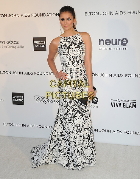 Nina Dobrev.The 21st Annual Elton John AIDS Foundation Academy Awards Viewing Party held at The City of West Hollywood Park in West Hollywood, California, USA..February 24th, 2013.oscars full length sleeveless dress white silver diamante black clutch pattern embroidered hand on hip.CAP/DVS.©DVS/Capital Pictures.