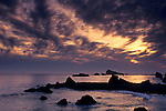 Sunset and clouds over coastal rocks and ocean at Cresent City, California