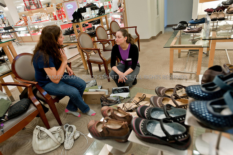 "9/23/2010--Seattle, WA, USA..Susan Haagen, 50, tries on shoes in the ""Comfort shoe"" department at Macy's in Bellevue Square in Bellevue, WASH. She is helped by store employee Amanda Ramlow, 24...Macy's in Bellevue,  WASH., near Seattle. After years of acquiring other department stores and trying to make them all look the same, retailers like Macy's and Saks are now trying to make each store seem local and authentic. The Seattle store, in Bellevue Square, has an Asian and Indian population, lots of corporate types and ""Microsoft wives,"" as the store manager referred to them. ..©2010 Stuart Isett. All rights reserved."