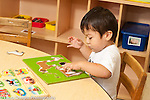 Education preschool 3 year olds boy sitting at table playing with wooden puzzle horizontal