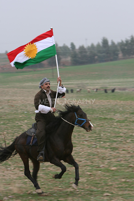 ERBIL, IRAQ: A man flies the Kurdish flag on horseback at a Kurdish wedding ceremony...Images from a traditional Kurdish wedding in Iraqi Kurdistan...Photo by Safin Hamid