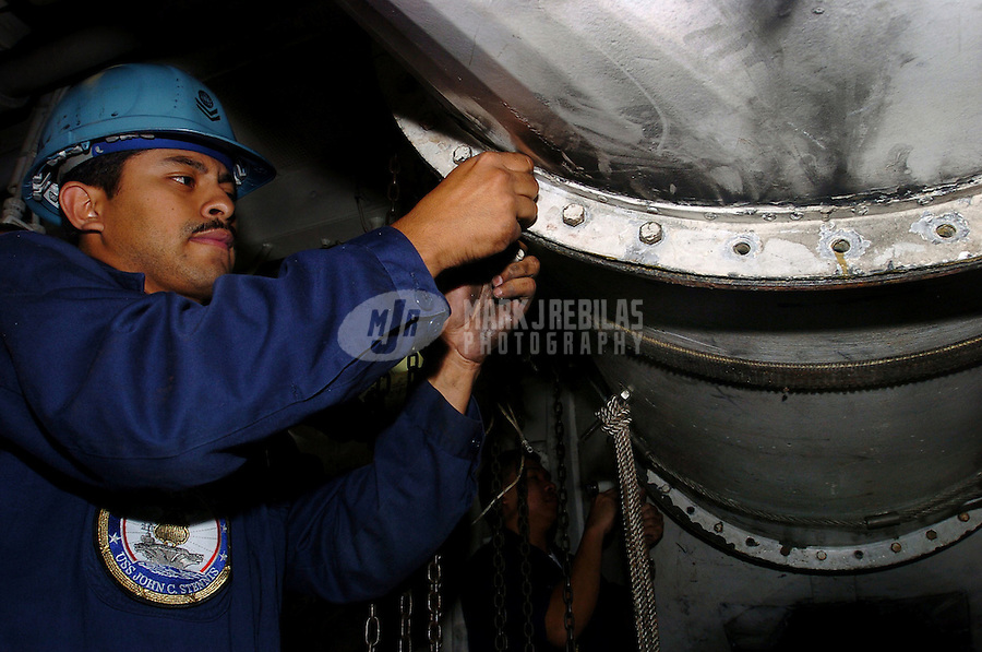 040624-N-6213R-025 Pacific Ocean (June 24, 2004) - Electrician's Mate 2nd Class William Quintanilla of Pico Rivera, Calif. secures a circulation air vent following repair work in a fan room aboard USS John C. Stennis (CVN 74).  Stennis and embarked Carrier Air Wing Fourteen (CVW-14) are currently at sea on a scheduled deployment.  Photo by Mark J. Rebilas
