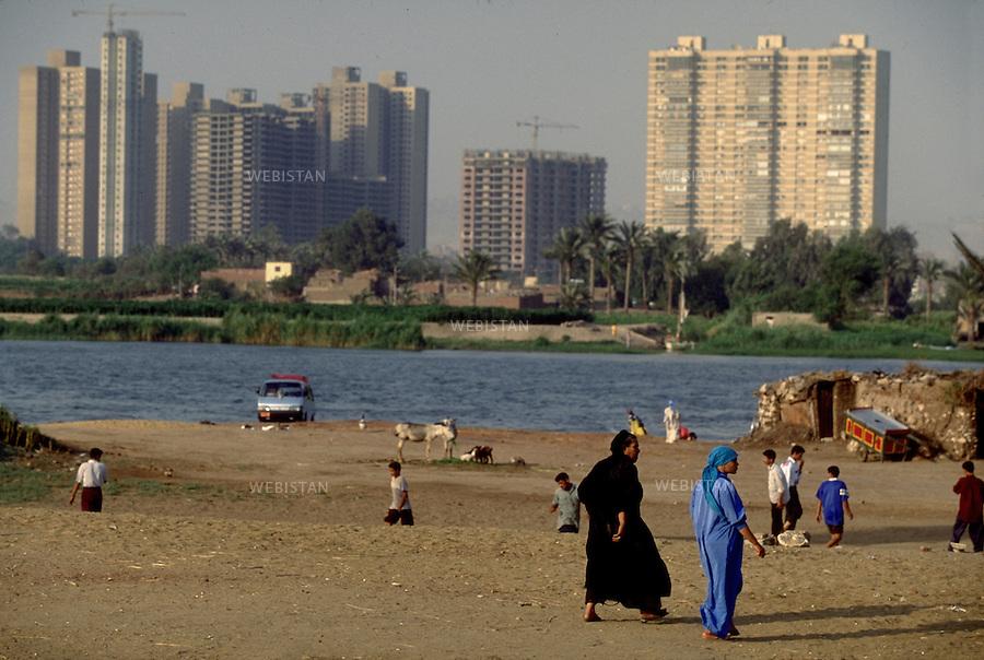 ..Egypt. Cairo. 1996. Egyptians walk along the Nile. On the opposite bank, skycrapers of Maadi District rise...Egypte. Le Caire. 1996. Des Egyptiens se promenent le long du Nil. Sur la rive opposee s'elevent les gratte-ciels du quartier de Maadi.