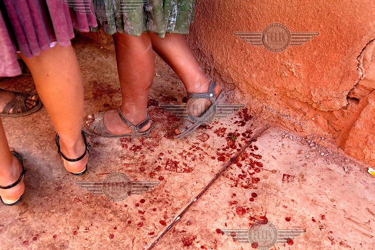Women stand next to drops of human blood on a pavement in Macha during the tinku festival. <br /> <br /> The people of Macha and surrounding communities carry on the pre-Columbian tradition of ritual fighting. The communities gather on the plaza of Macha to fight and dance in competition with each other. The blood that is spilled is an offering to Mother Earth. In return, the people ask for rain and a good harvest. This ritual is called tinku or fiesta de la cruz since the cross is also engaged in the festivities. The cross is dressed up, given offerings and brought from communities around Macha to the church in town. This syncretic festival melds pagan, pre-christian rituals with Catholic practice. /Felix Features
