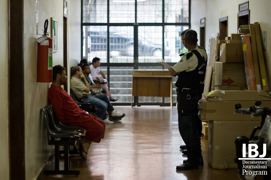 An arrested man spends a day at Forum, the civil and criminal courthouse in Divinopolis, Brazil. Prisoners at Forum usually come from Presidio Floramar, a prison for adults or Centro Socioeducativo, a jailhouse for youth. When prisoners from Centro Socioeducativo walk the halls of Forum they are accompanied by a guard but do not have to wear handcuffs, unlike their adult counterparts. Divinopolis is where 2008 JusticeMaker Dr. Aziz Saliba is producing his educational films on habeas corpus and the Inter-American Court to teach the public about their legal rights and inform the legal profession of their options to appeal cases to courts outside of Brazil.