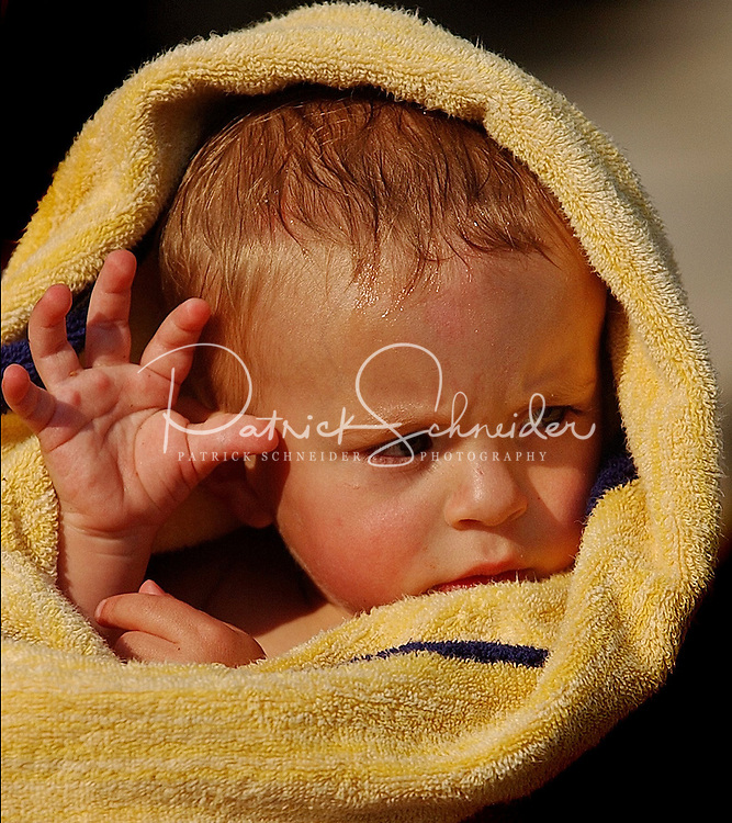 A young boy stays warm wrapped in a towel after swimming.