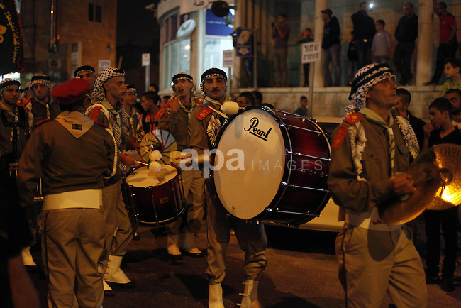 "Palestinian scouts play musical instruments as they parade through the streets during a celebrate the Eid-al-Adha, or ""Feast of Sacrifice,"" in Jerusalem city on October 13, 2013. Millions of Muslims around the world celebrate Eid al-Adha or Feast of the Sacrifice, which marks the end of the annual hajj or pilgrimage to Mecca and celebrates Abraham's readiness to sacrifice his son to God. Photo by Saeed Qaq"