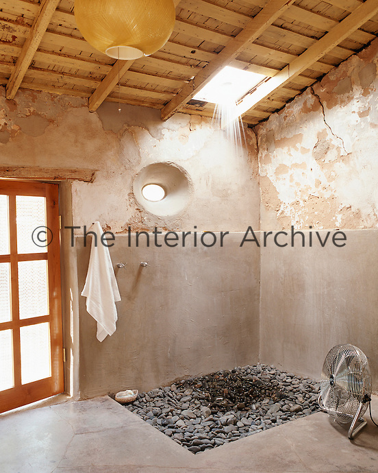 Loose Mexican beach pebbles provide a floor for the shower in the bathroom where the shower head is set directly into the skylight