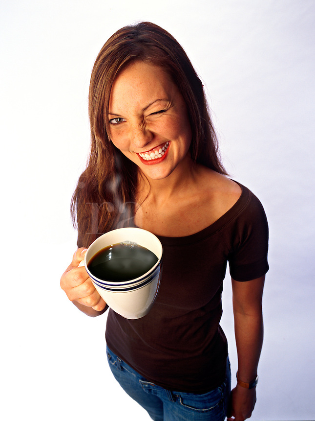 A young office worker playfully winks or squints at the camera as she holds her giant cup of coffee