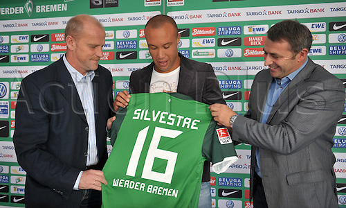 30.08.2010 German Bundesliga club SVWerder Bremen's new signed Mikael Silvestre (C)smiles with his jersey and his new club's head coach Thomas Schaaf (L)and sporting director Klaus Allofs (R)upon his presentation in Bremen, Germany, 30 August 2010. Bremen signed the 33-year-old defender from English side Arsenal on a free transfer.