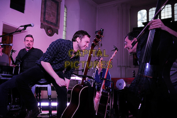 Phillip Phillips Winner of the eleventh season of American Idol, performing his first UK show, St Pancras Old Church, London, England. .11th March 2013.on stage in concert live gig performance performing music half length black blue check shirt guitar full 3/4 profile smiling   .CAP/MAR.© Martin Harris/Capital Pictures.
