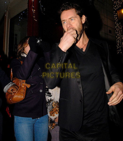 TAKE THAT - JASON ORANGE.Leaving the London Palladium after performing at the Royal Variety Performance, London, England..December 11th, 2008 .half 3/4 length black jacket coat eating apple fruit hand stubble facial hair fan camera taking picture photograph.CAP/IA.©Ian Allis/Capital Pictures.