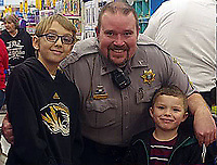 COURTESY PHOTO/Deputy Kyle Hackworth takes a moment from the excitement of Shop With a Hero to offer a smiling portrait with two children selecting Christmas gifts.