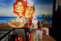 """Switzerland. Canton Ticino. Locarno. Bellavista Restaurant. On the wall, a drawing of Sophia Loren and Totò as a loving pizzaiolo ( a man who cooks pizza). The beautiful smiling woman holds in her hand a delicious pizza (mozzarella, tomato and basil leaves). The Gulf of Napoli and Mediterranean sea in the background. Sofia Villani Scicolone (born 20 September 1934), known professionally as Sophia Loren is an Italian film actress and singer. Antonio Griffo Focas Flavio Angelo Ducas Comneno Porfirogenito Gagliardi De Curtis di Bisanzio (15 February 1898 – 15 April 1967), best known by his stage name Totò or simply as Antonio De Curtis, and nicknamed il Principe della risata (""""the Prince of laughter""""), was an Italian actor, comedian, writer, poet, singer and lyricist. Santa Claus and Christmas gifts on the table. Father Christmas is the traditional English name for the personification of Christmas. Although now known as a Christmas gift-bringer, and normally considered to be synonymous with American culture's Santa Claus which is now known worldwide, he was originally part of an unrelated and much older English folkloric tradition. The recognisably modern figure of the English Father Christmas developed in the late Victorian period, but Christmas had been personified for centuries before then. 19.12.2019 © 2019 Didier Ruef"""