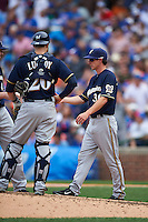Milwaukee Brewers manager Craig Counsell (30) makes a pitching change as Jonathan Lucroy  (20) looks on during a game against the Chicago Cubs on August 13, 2015 at Wrigley Field in Chicago, Illinois.  Chicago defeated Milwaukee 9-2.  (Mike Janes/Four Seam Images)