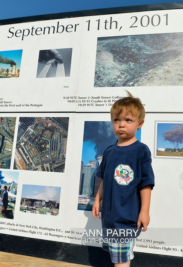 "East Meadow, New York, U.S. 11th September 2013. TIMOTHY HUNTER, 3, of Wantagh, visits the Global War on Terror ""Wall of Remembrance"" a traveling memorial on display in New York for the first time, at Eisenhower Park on the 12th Anniversary of the terrorist attacks of 9/11. Timothy's uncle Joseph G. Hunter, a firefighter in Squad 288 in Maspeth Queens, died during September 11th 2001 terrorist attack, and the nephew is wearing a T-shirt from the 9th Annual Memorial Drill for his Uncle Joseph. The unique 94 feet long by 6 feet high wall has, on one side, almost 11,000 names of those lost on September 11th 2001, along with heroes and veterans who lost their lives defending freedom of Americans over past 30 years. On the wall's other side is a timeline, with photos, covering 1983 to present day."