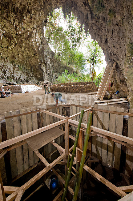 Wahyu Saptomo descends into a 4x4 meter wide dig, surpassing 6 meters in depth, at Liang Bua cave. LB1, the type specimen for Homo floresiensis, was discovered beneath the camera position.