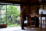 A visitor looks looks at a replica of the desk used by writer Lafcadio Hearn inside his old residence in Matsue, Shimane Prefecture, Japan on 05 Nov. 2012. Photographer: Robert Gilhooly.
