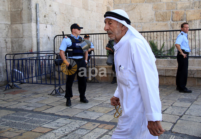A Palestinian man walks past Israeli policemen at the entrance of Damascus gate in Jerusalem's Old city on October 14, 2015. Seven Israelis and 30 Palestinians, including children and assailants, have been killed in two weeks of bloodshed in Israel, Jerusalem and the occupied West Bank. The violence has been partly triggered by Palestinians' anger over what they see as increased Jewish encroachment on Jerusalem's Al-Aqsa mosque compound. Photo by Mahfouz Abu Turk