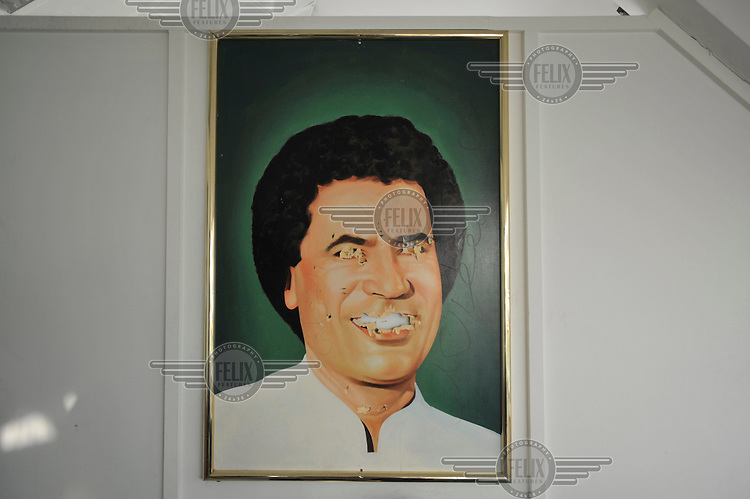 A defaced picture of Gaddafi in the House of the Green Book in Tripoli. After a six month revolution, rebel forces finally managed to break into Tripoli and have taken control of Bab al-Aziziyah, Col Gaddafi's compound and residence. Few remain that are loyal to Gaddafi in the city; it is seeming that the 42 year regime has come to an end. Gaddafi is currently on the run.