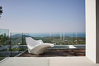 An iconic piece by Philippe Starck adds some welcome curves to soften the geometric lines of the roof terrace's architecture. The glass panels ensure that the stunning view is not hampered by a bulky safety rail.