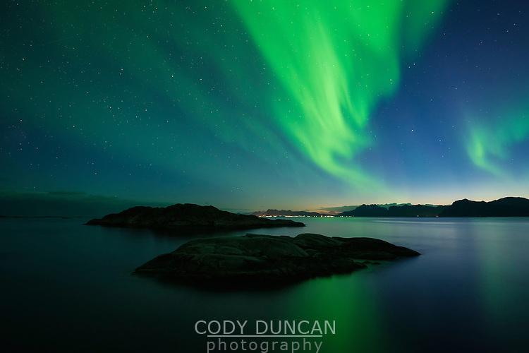 Northern Lights - Aurora Borealis fill sky over coastline, Austvågøy, Lofoten Islands, Norway