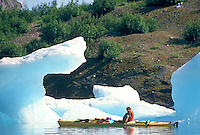 Woman kayaker amidst ice bergs, Bear Glacier, Kenai Fjords National Park, Alaska