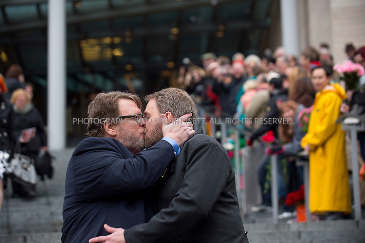 12/9/2012--Seattle, WA, USA...Grant Thornley, left, and Tim Keber kiss as they walk down the stairs of Seattle City Hall. .On the first day same sex couples were allowed to marry in Washington State, Hundreds of well-wishers braved cold and rain to celebrate 133 weddings at Seattle City Hall. Washington, Maine and Maryland last month became the first U.S. states to extend marriage rights to same-sex couples by a popular vote, in a leap forward for gay rights. A crowd of several hundred people waited outside City Hall in the cold to cheer couples as they descended the steps, some throwing bird seed, rice, blowing bubbles and handing flowers to the newlyweds...©Stuart Isett. All rights reserved.