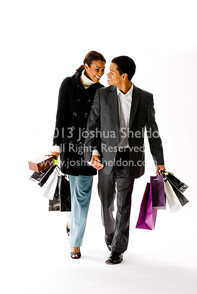 Young couple carrying shopping bags on white background