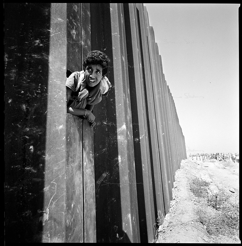 Rafah, Gaza strip, Sept 14 2005.Palestinians find gaps in the the 8 meter high wall  separating the Palestinian city from Egypt. Thousands  rushed across the border in an incredible chaos to visit relatives for the first time in 18 years or ... to bring back cheap Egyptian goods such as cigarets or gazoline.
