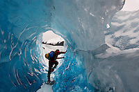 Hiker climbs through tunnel in melting Mendenhall Glacier in Southeast Alaska.<br /> Ice is exposed from thousands of years of being buried.