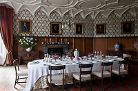 The dining room is hung with family portraits against wallpaper designed by A.W.N Pugin for the houses of parliament