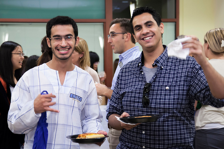 Abdul, an international student from Saudi Arabia studying Law, right and Faizal, also from Saudi Arabia studying Economics, enjoy pizza during the Global DePaul Carnival in the DePaul Center concourse Friday, Sept. 18, 2015. International students from different countries discovered the many opportunities and organizations that DePaul's International Programs Office had to offer. Student organizations had a chance to promote themselves and students from different countries were able to mingle and make new friends. (DePaul University/Josh Woo)