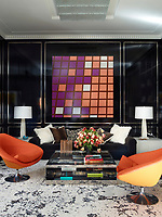 In the library, vintage Svensson swivel chairs flank a circa-1980 cocktail table by Joseph D'Urso for Knoll; a painting by Sarah Morris hangs above the custom-made sofa, the walls are panelled with nickel-inlaid ebonized mahogany and the rug is by Beauvais Carpets.