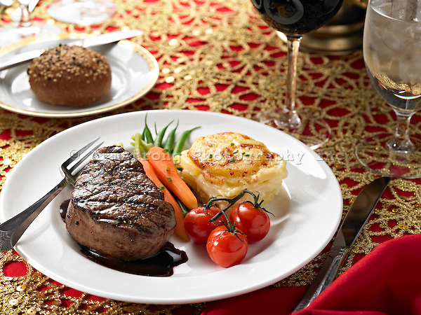 A dinner plate with filet mignon, carrots, potatoes, and cherry tomatoes. Elegant, formal place setting.